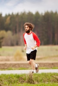 A runner with long hair and beard jogging in the country